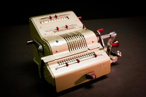 Front view of a mechanical calculator that is silver in color with red knobs.