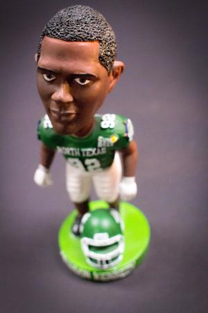 Bobblehead of an African American man in a green football uniform, his helmet laying at his feet. The bobblehead is standing on a light green platform.