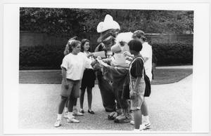 Black and white photo of several students surrounding someone in an eagle costume and someone in an armadillo costume. The eagle is signing someones paper.