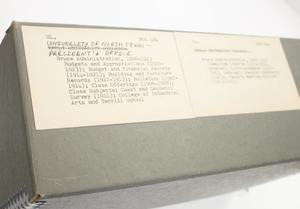 Closeup of a white slip with a bit of text on it. It is on a grey box.