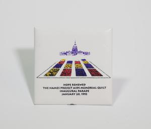 A white, square-shaped button. The top shows the capitol building, and under it a drawing of the quilt memorial on it.