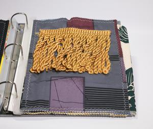 An open binder with fabric pages. The page shown is a patched dark fabric, golden thread on top of it.