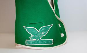 Closeup of a patch with an eagle and the words Green Jackets on it, on a green vest.