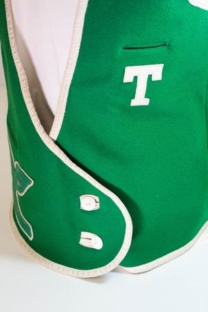 Closeup of a green vest rimmed with white. There is a white T on it.