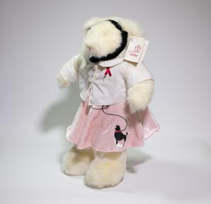A white fuzzzy bear wearing a white shirt, a pink skirt and a headset. It has a tag on its left ear that says AIDS Resource Center. Seen from the side.