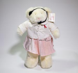 A white fuzzzy bear wearing a white shirt, a pink skirt and a headset. It has a tag on its left ear that says AIDS Resource Center. Seen from the front.