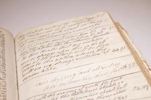Closeup of a page on the right side of an open book, filled with cursive handwriting.