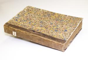 Book with a worn brown spine and a cover with different colors consisting of brown, yellow and blue.