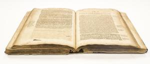 View of an open book, the pages old and worn. The pages it is opened to are filled with black text.