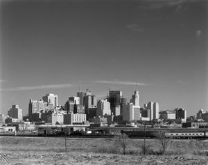 Black and white photograph of a city skyline with many skyscrapers and buildings grouped together in a big mass. A field of grass and some shrubs are seen in the foreground, and a train runs on a track across the image below the city.