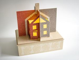 A book pop-up on the top of a light brown paper box, with the pop-up being shaped like a house. The left side of the pop-up is orange, the right side grey.