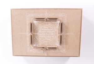View of the top of a box. It is a light brown color with white writing shaped into a box. In the middle is a circle, filled with more white writing.
