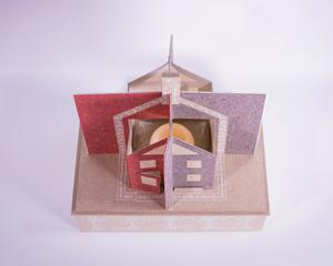 The top of a box with a pop-up made to look like a house. The pop-up is  red on the left side, and pink on the right.