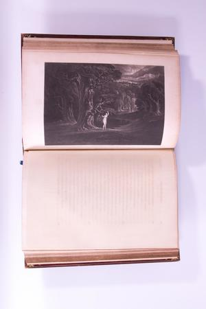 Open book, the page on the left is a black and white picture of what appears to be a cave. The page on the right is blank.