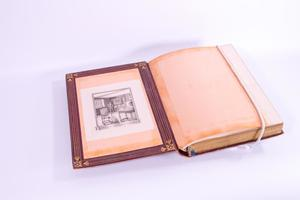 Open book. On the left side of the page is a drawing of a room. It is framed by the cover of the book which is red with thin gold lines. The right side of the page is blank, with a string over it attached to the book.