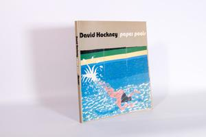 Front of book. The book has a grey cover, with a painting of a mermaid like figure on the front in simplistic colors. The book title is above the painting.