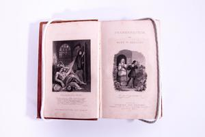 Open book. The left side of the page is a painting of a muscular man with no shirt on top of what appears to be on a skull. Behind him on the right is someone holding a spear. On the right page is another drawing and the book title. The drawing is of a woman standing in the doorway, someone else walking out of that same door.