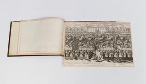 Picture layed on top of an open book. The picture is of a group of people lined up ready to march. A building can be seen in the back.
