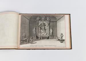 Right page of a book. The page is a drawing of a room with a giant painting as the center of the drawing. It is framed, with a statue on each side of it.
