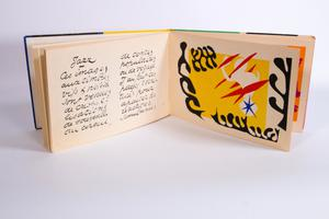 An open book with curvy writing on the left page. On the right side of the page is a graphic with red, yellow, white and black colors.