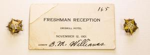 A white card, folded on the top left corner. It says Freshman Reception on it and has the number 165 on the top right corner. Next to the card, on each side, is a golden star pin.