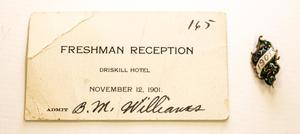 A white card, folded on the top left corner. It says Freshman Reception on it and has the number 165 on the top right corner. Next to the card on the right side is a pin with the number 1901 on it.