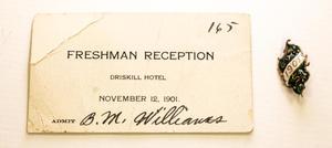 """Una tarjeta blanca, doblada en la esquina superior izquierda. Dice """"Recepción de estudiantes de primer año"""" en ella y tiene el número 165 en la esquina superior derecha. Junto a la tarjeta en lado derecho hay un pasador con el número 1901."""