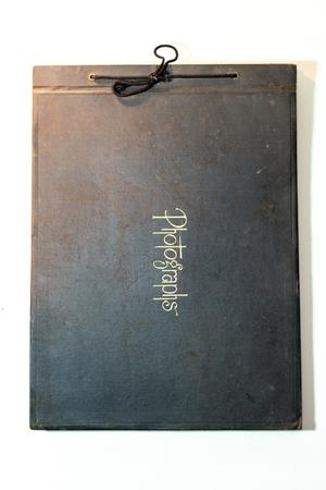 A black album tied together by a string on the spine. The middle of it says the word Photographs.