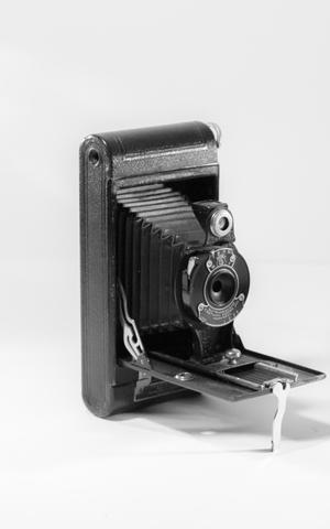 Black pocket camera, open with the open lid propped by a small white handle.