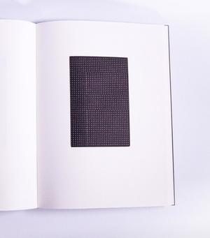The right page of an open book is seen. In the middle is a black rectangle filled with white dots.