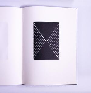 The right page of an open book is seen. The page is white, except for the black rectangle in the middle, white lines on each side.