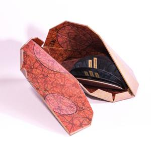 A chrysallis shaped box, reddish in color. It is opened up so we the inside is seen, black half circle pages inside.