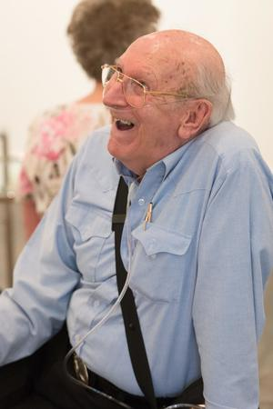 Old man in a blue shirt and tubes around his nose. He wears gold glasses and smiles to the left of the picture.