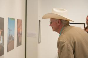 A man in a coat and cowboy hat faces a wall of photos in front of him. He leans forward as he looks at them.