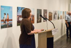 A woman with short hair and wearing a dress stands behind a podium with a microphone. A wall of photos is behind her.
