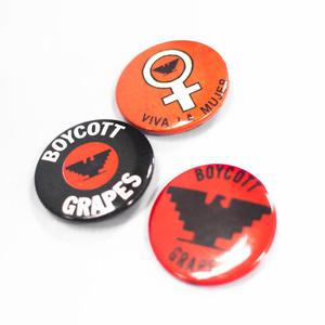 Three buttons, one black, one red, and one orange. The black one says  Boycott at the top and Grapes at the bottom in white letters. The orange  one has a white female symbol, the red one says Boycott Grapes in black.