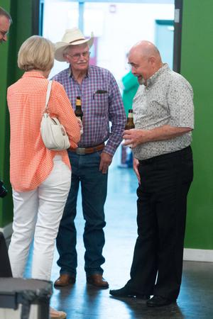 Two men and a woman stand in a circle. The woman is on the left and seen from the back with an orange plaid shirt. Both men have a beer in hand.
