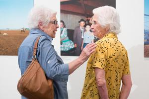 Two older women stand by each other and facing one another. They are seen from the back, but their posture shows the sides of their faces. The woman on the left has on a blue shirt and brown purse. The woman on the right has on a yellow shirt. They are in front of a gallery wall.