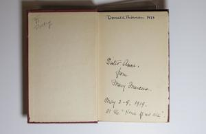 Open book showing the inside cover. The left side is blank except for writing in pencil in the top left corner. The right page has a name written at the top, the bottom half of the page containing more handwriting.