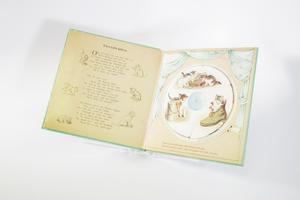 """Book opened up with the page on the right containing a circular illustration of kittens, one of them inside of a boot, some of them by a book. The illustration is made movable. The page on the left contains a poem titled """"Three Little Kittens."""""""