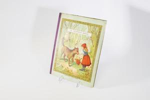 Cover of a book with an illustration of Little Red Riding Hood, holding a basket in front of her with a brown wolf in  front of her. They stand in the middle of the woods. The illustration is framed by a thick golden design, on a gray cover.