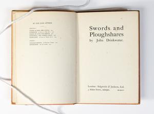 A book open to two pages. The page on the left has short amount of text at the top, the page on the right is the title page.