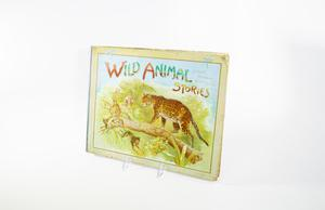 A worn cover of a book containing an illustration of a leopard perched on a tree branch, four monkeys in the tree in front of it. The leaves of the tree surround them and the bright blue sky is above them. The title of the book is at the top in colorful letters.
