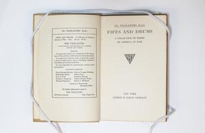 Open book, the page on the left containing text in a box. The page on the right is a title page.