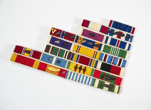 A rack of ribbon which consists of about 22 ribbons held together in eight descending rows starting with one at the top on the right and four at the bottom. Many of them have stripe, and they are all made up of different colors.