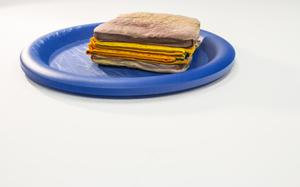 Book pages made to look like a stacked grilled cheese sitting on a blue plate.