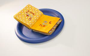 Book pages made to look like a grilled cheese sitting on a blue plate. It is open to two yellow pages. The one on the left has a design of orange and white circles.