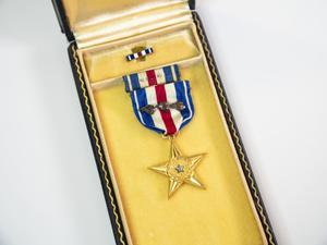 A medal in the shape and color of a gold star, with a mini silver star  in the middle. It is hanging from a red white and blue striped ribbon,  inside of a box with a gold inside.