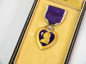 A medal in the shape of a gold heart with the inside of it purple with  the figure of a head in gold. The medal is attached to a purple ribbon  and is laying on a gold surface of the inside of a black box.