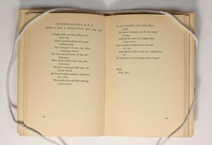 Open book, the page on the left containing a small poem title In Memoriam at the top, the poem continued on he right page. The bottom section of both pages is blank.